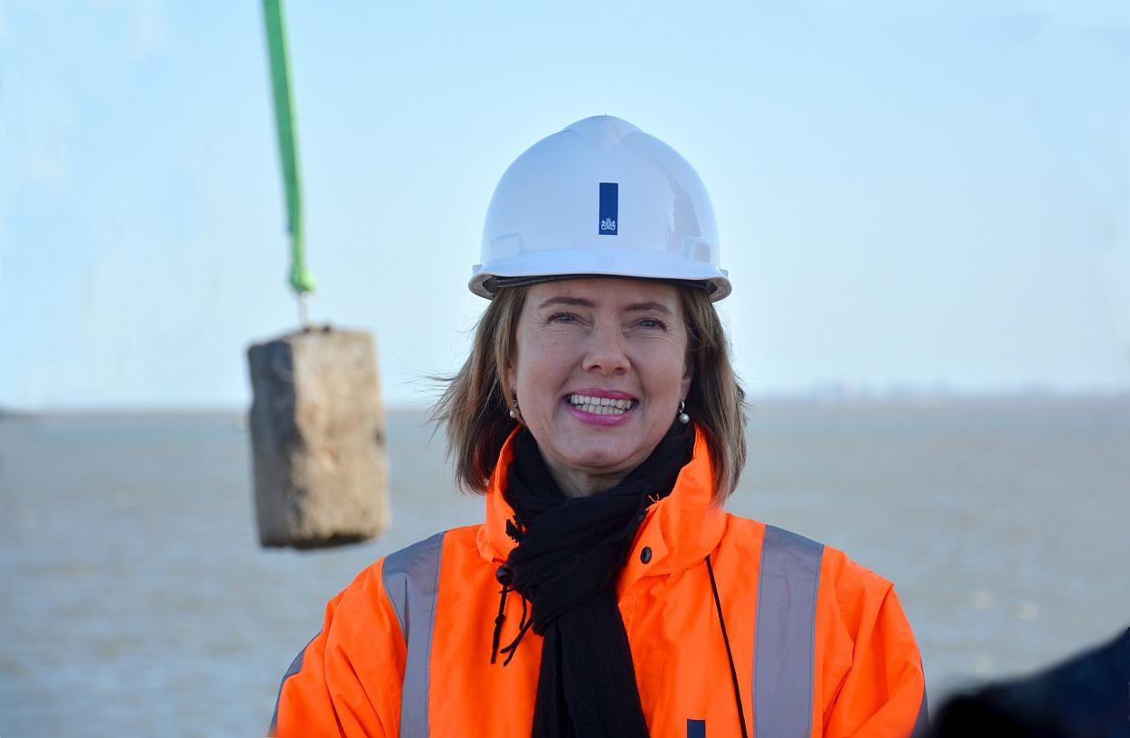 Minister Cora van Nieuwenhuizen van Infrastructuur en Waterstaat verwijderde de eerste oude basaltsteen uit de 'oude' dijk. 'Een oer-Hollands project. Hier staat een heel trotse minister', zei zij. (Foto: Gijs van Hesteren)